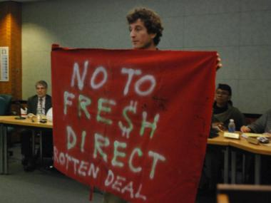 Rob Konrad, a critic of the FreshDirect deal, holds up a sign at a public hearing on the FreshDirect subsidy deal in February 2012. On June 13, several South Bronx groups filed a lawsuit against the company.