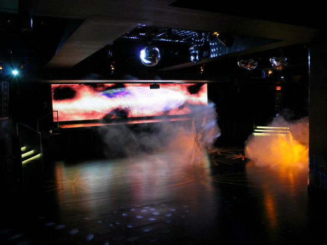 The main dance floor of XL, complete with smoke machines, disco balls, and a massive LED screen.