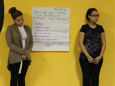 Cheyenne Lee, 18, and Mireya Ruiz, 17, presented a poster during a community meeting on Feb. 16, 2012, which listed their concerns with a city plan to move a new charter school into their high school building.