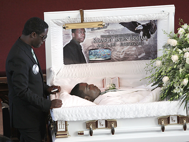 Franclot Graham, the father of slain teenager Ramarley Graham stands over his son's open casket on Sat., Feb. 18, 2012.