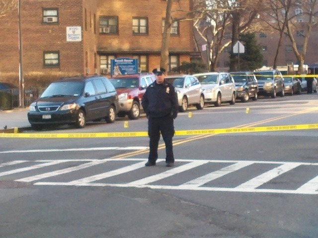 A police officer stands guard after cops and a suspect had a shootout near Columbia St. on the Lower East Side on Feb. 27, 2012.