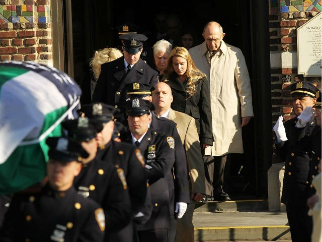 Mourners follow the flag-draped casket of NYPD officer Peter Figoski, who was killed last week while responding to a robbery, as its brought out following his funeral at St. Joseph's Church on December 19, 2011 in Babylon, New York.