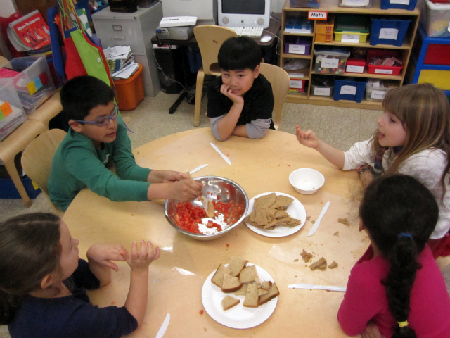 <p>Students stir a tomato mixture during a cooking lesson at the East Village Community School, one of the schools in District 1.</p>