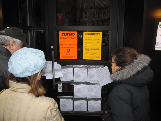 Passers-by stopped to read court documents posted on Papasito's front door after cops shut down the restaurant on Friday March 2012.