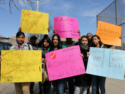 Students from Schomburg hold up signs shortly after walking out of their school to protest the DOE's co-location plan.