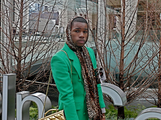 Cameron B. in a vivid green double-breasted jacket, metallic man purse, and leopard scarf.