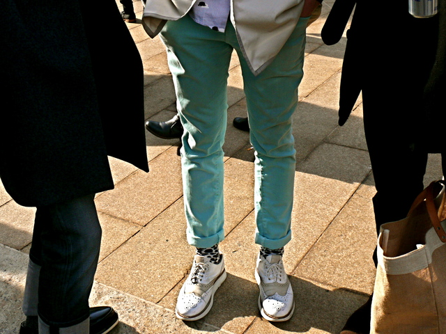 Julian B. wears sea foam green cotton pants with white suede wing tip shoes.