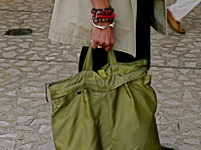 A utilitarian olive green nylon tote with mixed arm accessories.