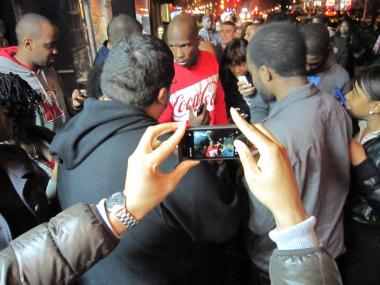 New England Patriots receiver Chad Ochocinco is surrounded by fans he invited for dinner at Sylvia's Restaurant in Harlem.