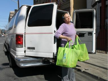 Heidi Hynes, executive director of the Mary Mitchell Center, delivers two produce-filled tote bags to members of the La Canasta food-buying club.
