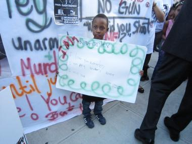 Ramarley Graham's brother Chinnor Campbell held a sign at a protest in front of the 47th Precinct in the Bronx.
