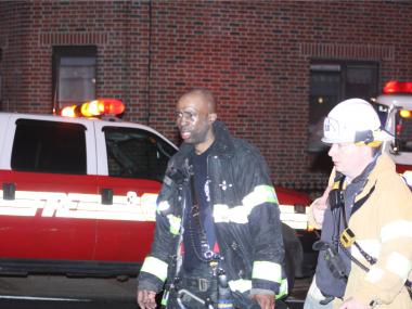 An EMT tends to a firefighter at the scene of a third alarm blaze at 65-55 Maurice Ave. on March 27, 2012.