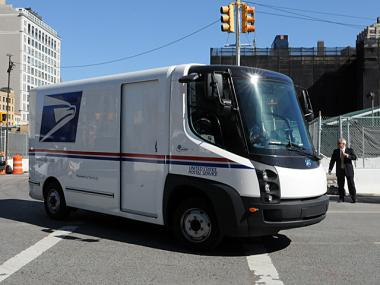 A sleek USPS mail truck design is seen entering the Javits Center.