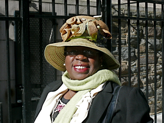 Mattie S. wears a medium brimmed straw hat with ribbon like motif and grassy green accents.