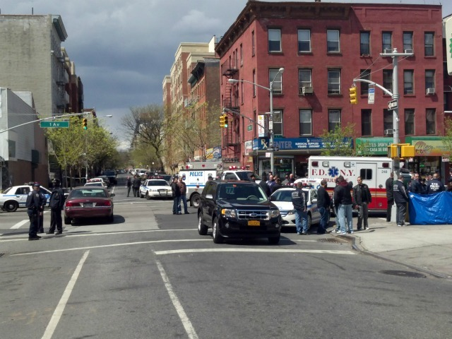 Police shot and killed a man robbing an East Harlem pharmacy and were hunting for another alleged robber.