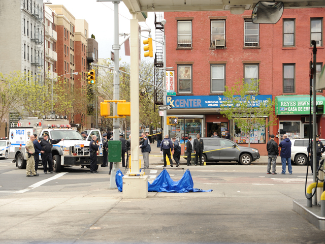 The blue tarp marks the spot where the suspect was shot on April 12, 2012 as he fled the pharmacy on First Avenue.