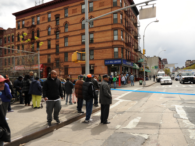 People stand on the edge of the crime scene at First Avenue and East 119th Street.