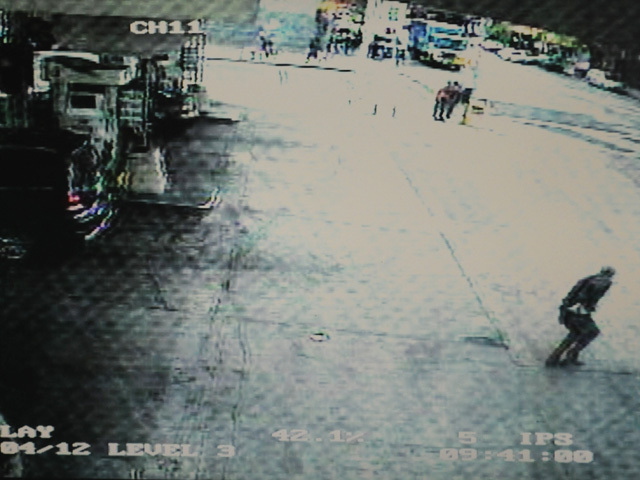 A still from the surveillance video at the gas station shows a man in the lower right corner — a retired lieutenant — reaching for his gun as the robbery suspect runs from the scene.