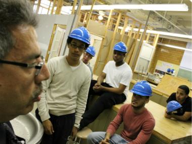 Phil Gazard, a longtime Gompers teacher, helped his class construct the four-room structure visible behind the students.