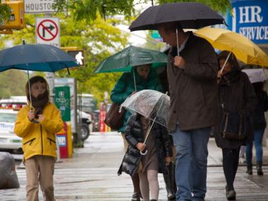 New Yorkers brave the rain and hold umbrellas on Allen and Delancey streets on April 22, 2012.