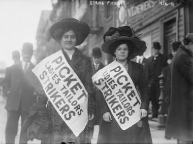 Two women strikers from the Ladies Tailors union stand on the picket line during the