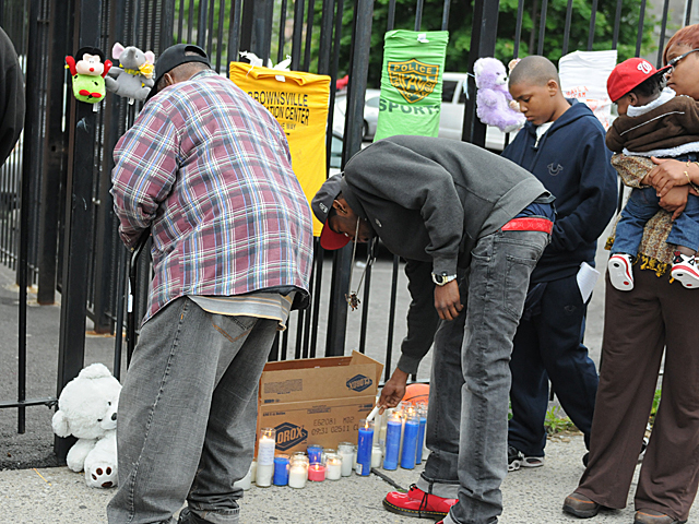 Mourners light candles at a memorial for Yakim McDaniels, May 7, 2012.