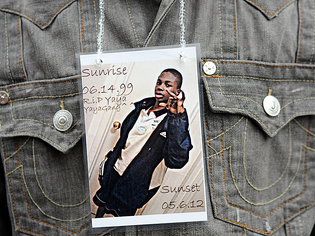 A friend of Yakim McDaniels wears a photo of the 12-year-old during a vigil on May 7, 2012.