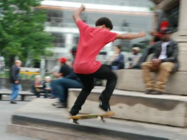 A skateboarder skates through Columbus Circle.