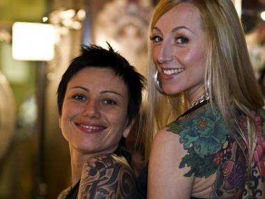 Two women show off their tattoos at the New York City Tattoo Convention.