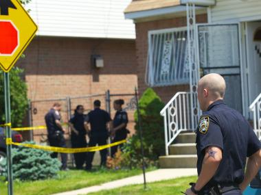 Cops stand guard near a Springfield Gardens home where a girl was stabbed on May 29, 2012.