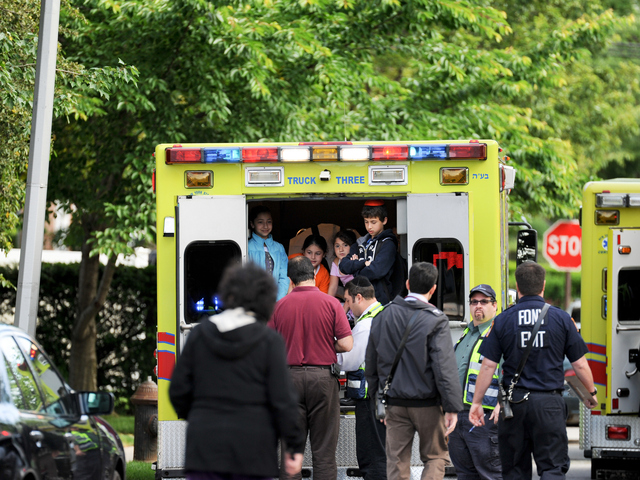 <p>Paramedics check out children from the school bus crash on Tuesday June 5, 2012.</p>