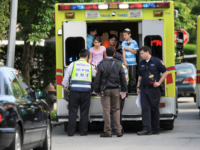 <p>Ben Azulai, 10, at right, with his 9-year-old sister Leeanne, is checked out by paramedics.</p>