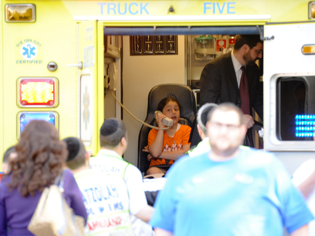 <p>A child uses a phone in an ambulance at the site of the crash on Tuesday June 5, 2012.</p>