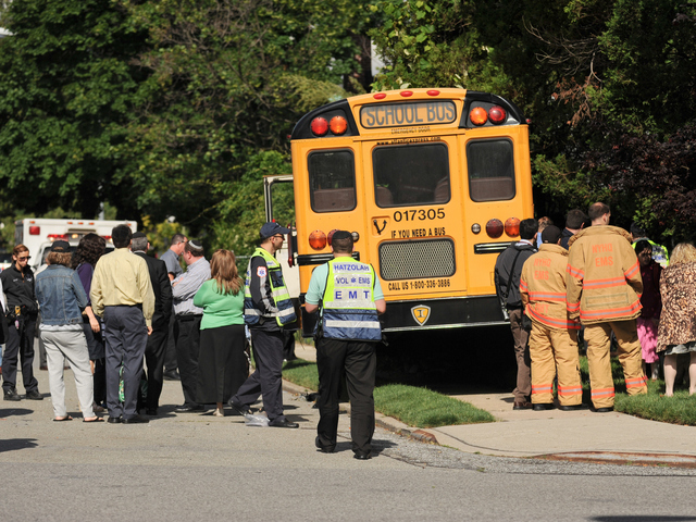 <p>Emergency workers and parents gather around the crashed school bus on Tuesday June 5, 2012.</p>