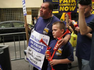 Sammy Morales, at left, with his 9-year-old son, Sammy Jr., during the protest on Thursday, June 7, 2012. Morales has been out of work for a year because of the strike at 350 E. 52nd St. in Midtown East.