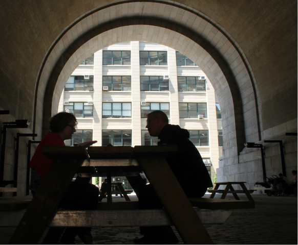 Two people enjoy lunch on the new picnic tables in The Archway.