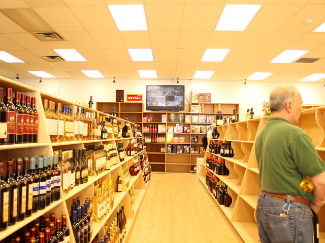 A customer browses through the aisle at Wine House in Rego Park.