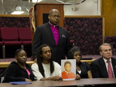 Rev. Dr. Victor Brown with the family of Vaughan Mitchell, 15, who drowned last week in the waters near Jersey Street and Richmond Terrace.