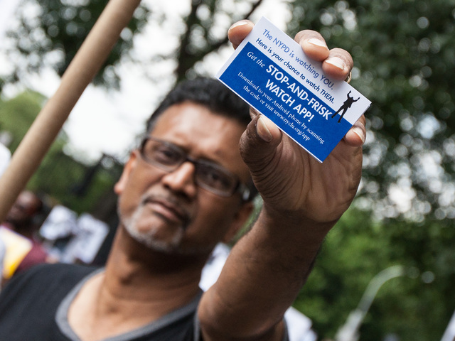 "A protestor displays a card for the ""Stop-and-Frisk"" phone 'app' at the Silent March on June 17th, 2012."