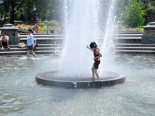 Children play in the fountain at Washington Square Park.