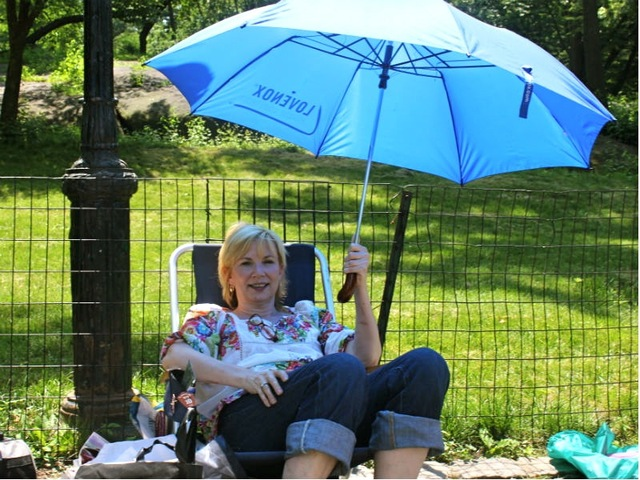 Nancy Reynolds, 52, of Wood Cliff Hills, NJ, tried to beat the heat in Central Park with a blue umbrella on June 20, 2012.