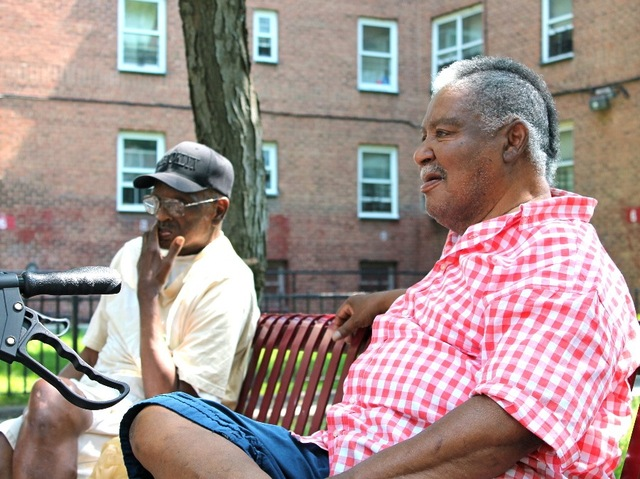 William Lewis, 84, and Frederick Waters, 69, sit beneath a tree outside the Red Hook Houses.