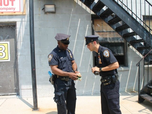 Two police officers acting out a training skit demonstrate the proper procedures during a drug find.