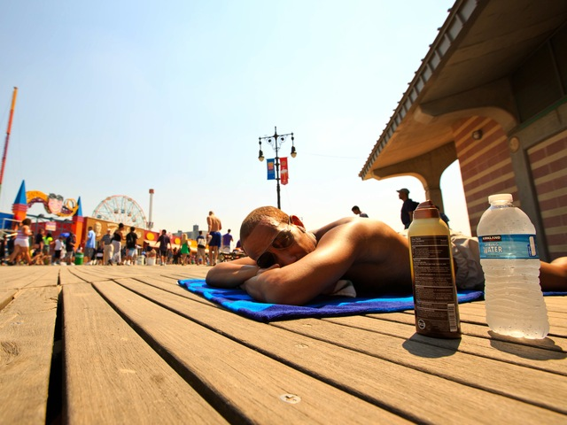 <p>Julius Chase, 23, from the Upper West Side, try to tan himself at Coney Island Beach on June 21, 2012, while attending a rehearsal of a music video filming.</p>