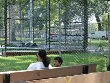 Ricki Martines, 32, and his 3-year-old son, Ricki Jr., watch sprinklers spray water just beyond reach, on the other side of a chain-link fence.