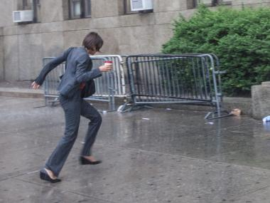 A young woman runs for cover during today's rain storm in lower Manhattan on June 22nd, 2012.