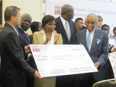 Charles Rangel holds a check from the West Harlem Local Development Corporation that wil be used to fund 500 jobs for West Harlem youth.