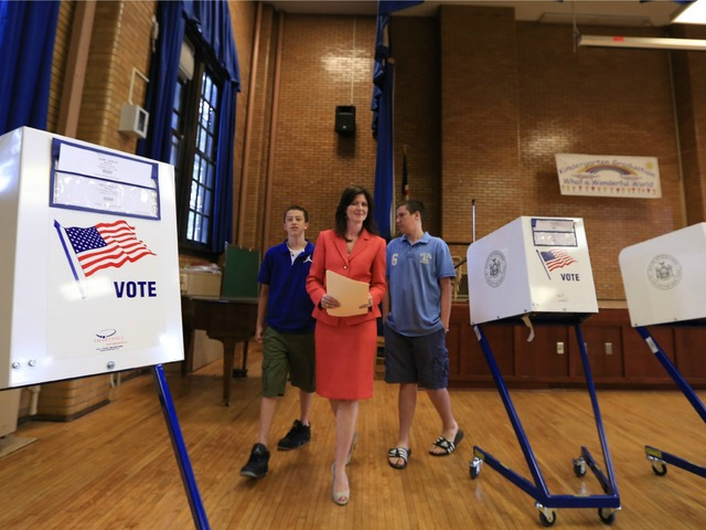 Councilwoman and Congressional candidate Elizabeth Crowley, flanked by her two sons, casts her vote on Tuesday, June 26, 2012, at P.S. 113 in Queens.