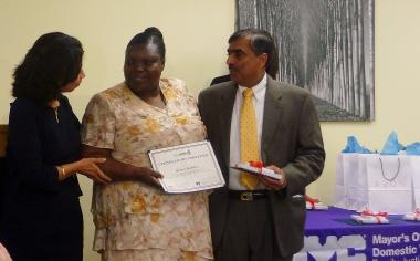 Bronx resident Marjorie Brailsford accepts her NYC STEPS certificate from Yolanda Jimenez, Commissioner of the Mayor's Office to Combat Domestic Violence (left) and DoITT Commissioner Rahul Merchant, on June 27, 2012.