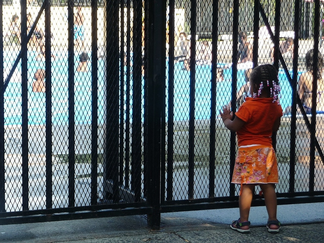 A girl watched swimmers through a fence at Claremont Park Pool in The Bronx.